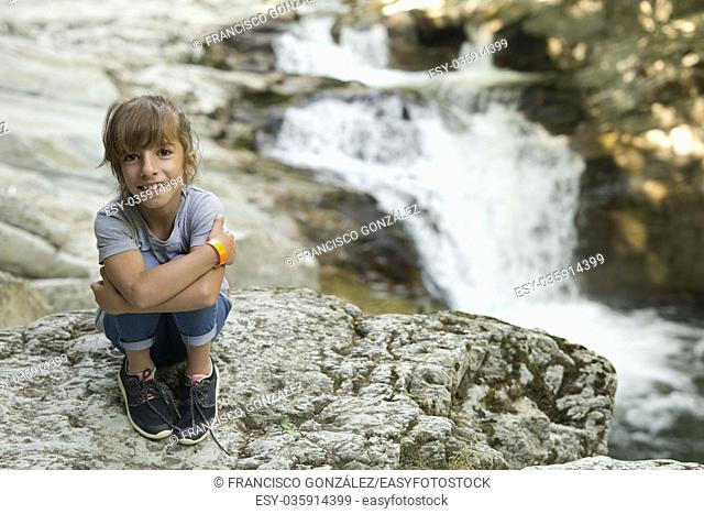 Girl sitting on a rock next to the Waterfall of the bucket in the Selva de Irati in Navarra, Spain