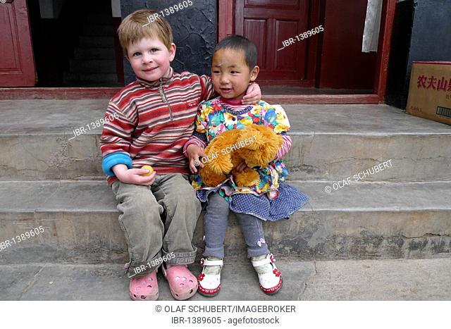 Encounters in Tibet, young European girl hugging a little Tibetan girl and her teddy-bear on stone steps, Lhasa, Tibet, China, Asia