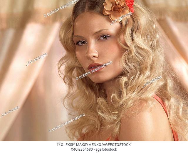 Beauty portrait of a young woman with a flower in her beautiful blond hair