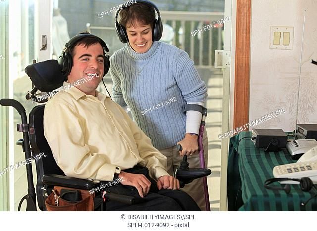 Couple with Cerebral Palsy using headphones with their radio