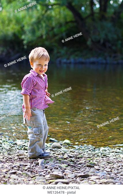 Little boy playing with water and rocks on the shore of River Sieg, Germany