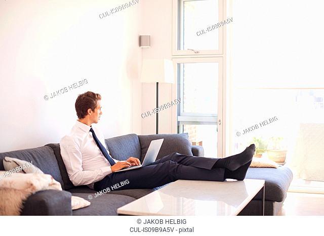 Businessman sitting on sofa using laptop