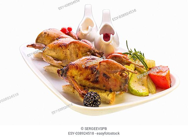 Roasted quail with vegetables on white background