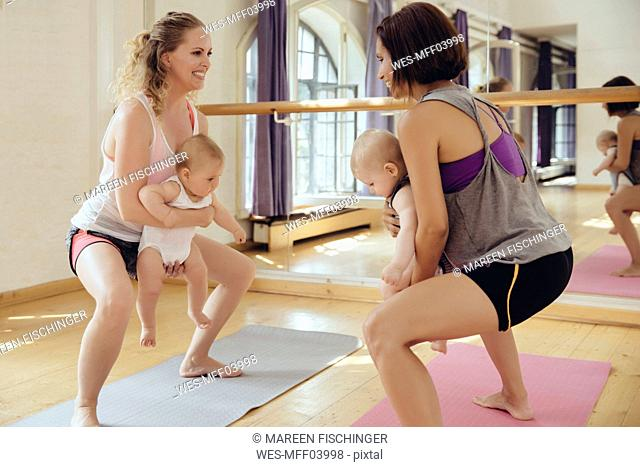 Two mothers working out on yoga mats with babies in their arms