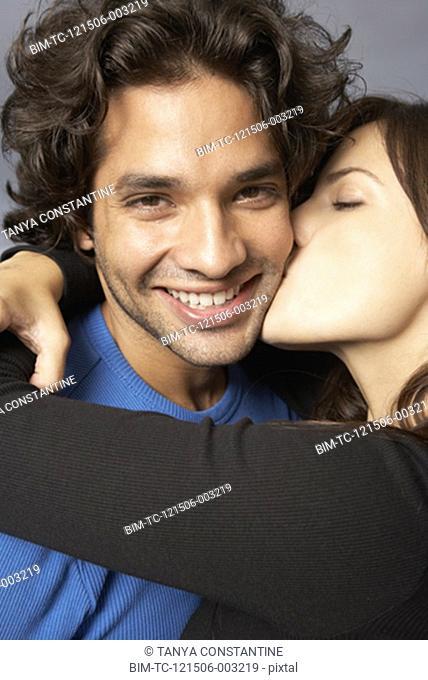 Hispanic woman hugging and kissing boyfriend