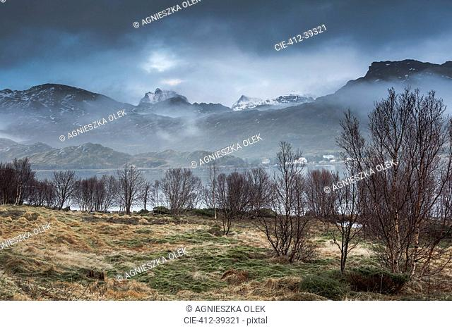 Fog around calm, rugged mountains, Andopen, Lofoten, Norway
