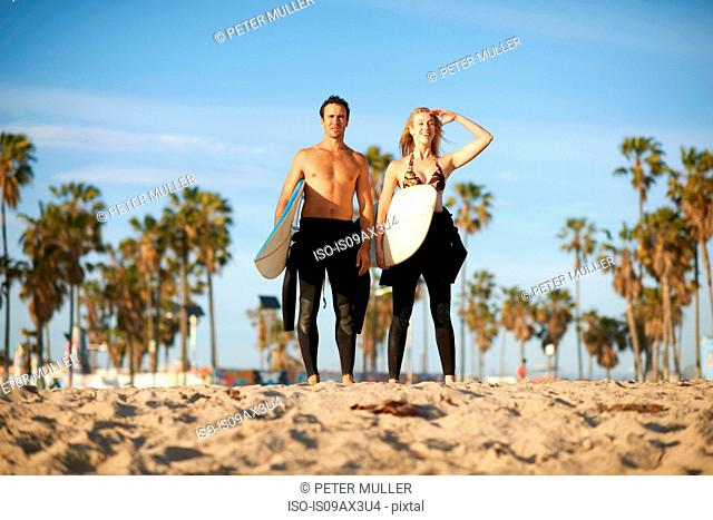Surfing couple with surfboards looking out from Venice Beach, California, USA