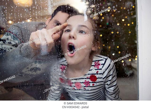 Playful father and daughter drawing in condensation on wet winter window