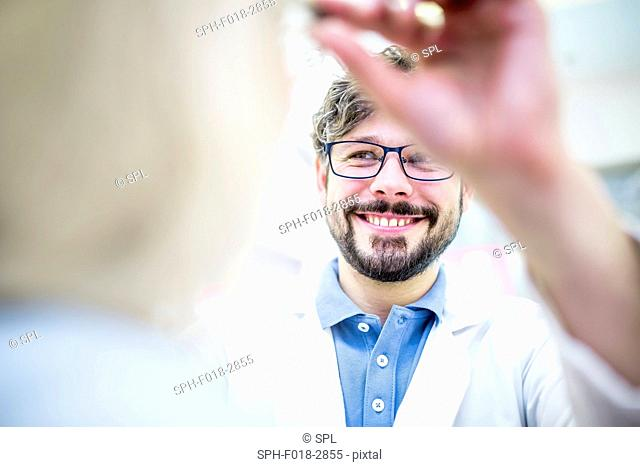 Optometrist trying glasses on woman in optometrist's shop