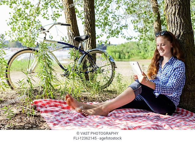 Teenage girl sitting on picnic blanket using a tablet at Woodbine beach in summer; Toronto, Ontario, Canada