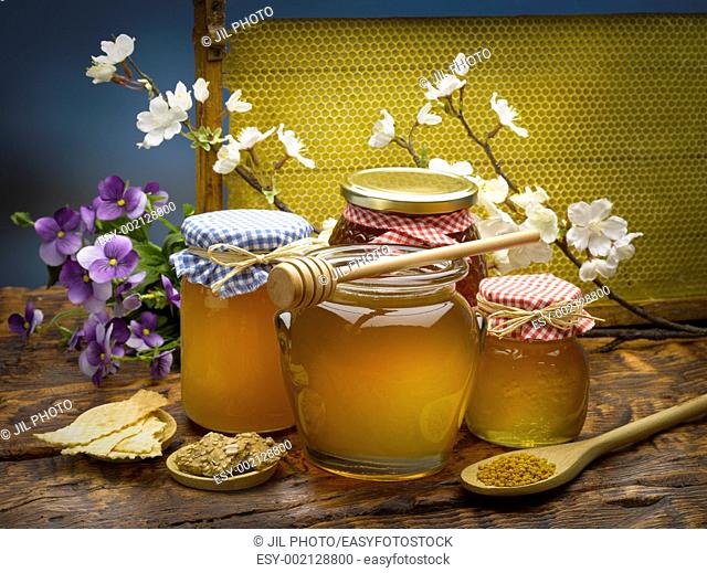 still life of jars of honey and pollen with a spoon