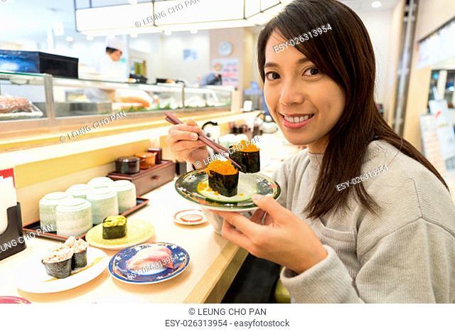 Woman enjoy sushi at japanese restaurant