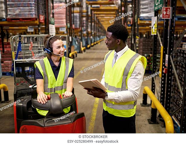 Warehouse manager and woman on tow tractor in discussion