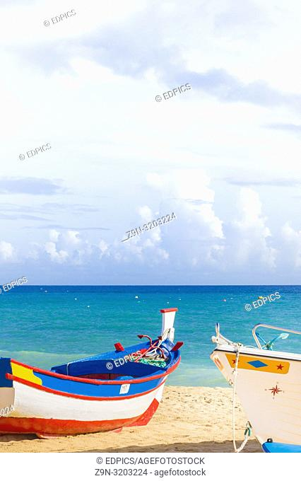 fishing boats painted in traditional colors on the beach, armacao de pera, algarve, portugal