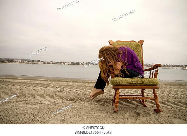 Woman sitting in armchair on beach
