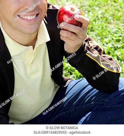 Close-up of a man holding an apple and smiling