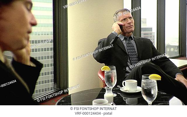 CU, Lockdown, Focus on Background, Two businessmen sitting at a table and using mobile phones