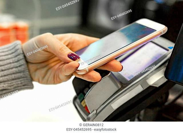 Female paying with NFC technology on smart phone, hands close up. Woman using mobile phone for pay by the bill