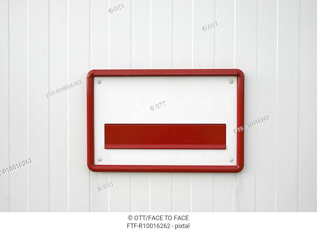A red and white letter opening attached to a white door