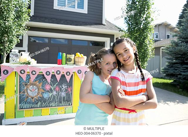 Portrait smiling girls standing in front of lemonade stand in sunny driveway