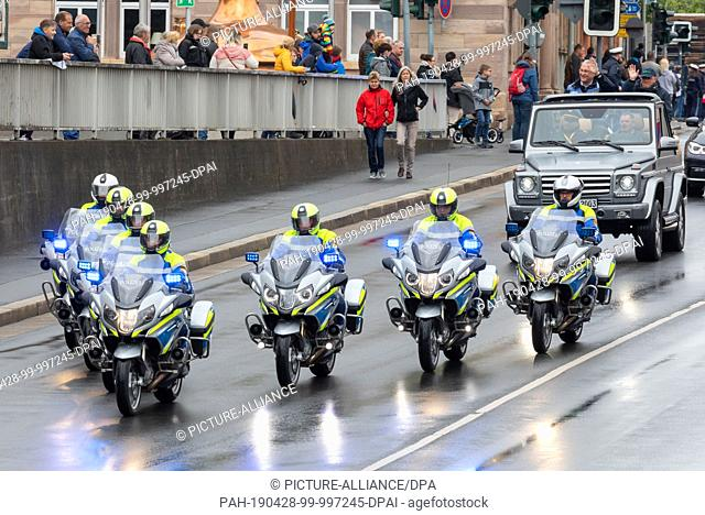 28 April 2019, Bavaria, Kulmbach: Police motorcycles drive in front of Joachim Herrmann (CSU), Minister of the Interior, in a cabriolet during the traditional...
