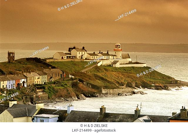 Houses and lighthouse on shore in the evening, Roche's Point, County Cork, Ireland, Europe