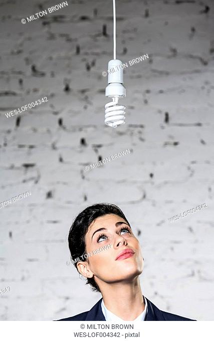 Businesswoman looking up at energy-saving lamp
