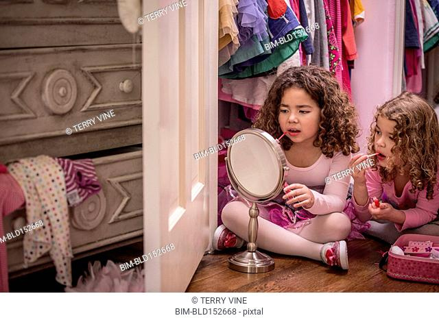 Girls playing dress up and applying lip gloss in mirror
