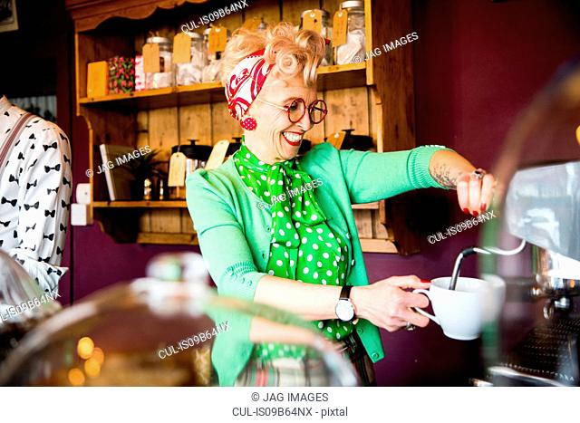Quirky vintage mature woman working behind tea room counter