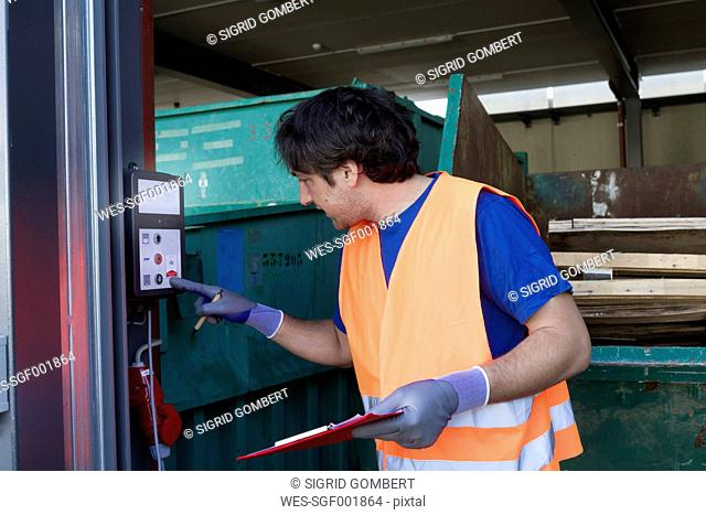 Worker at a waste container operating machine