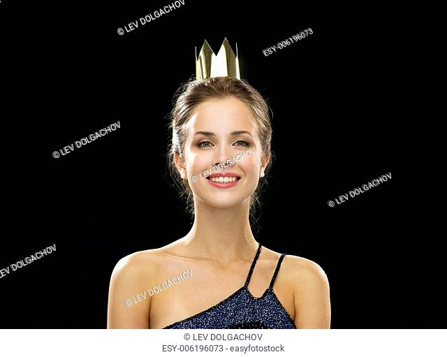 people, holidays, royalty and glamour concept - smiling woman in evening dress wearing golden crown over black background