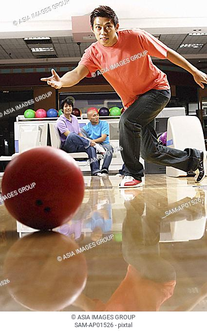 Man bowling, people sitting in the background