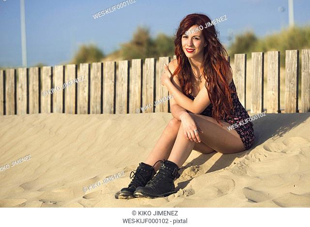 Spain, Cadiz, portrait of young redheaded woman sitting on the beach