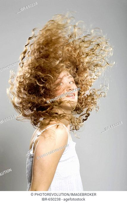 Young woman, her long curly hair flying through the air