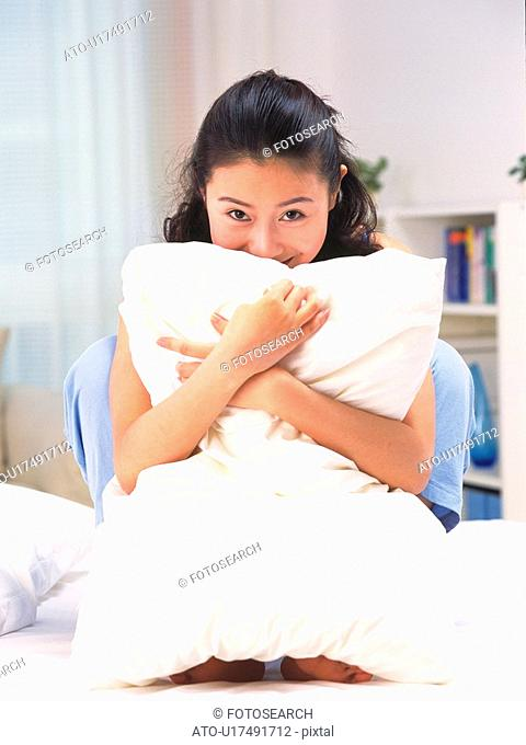 Woman clutching a pillow to chest on bed