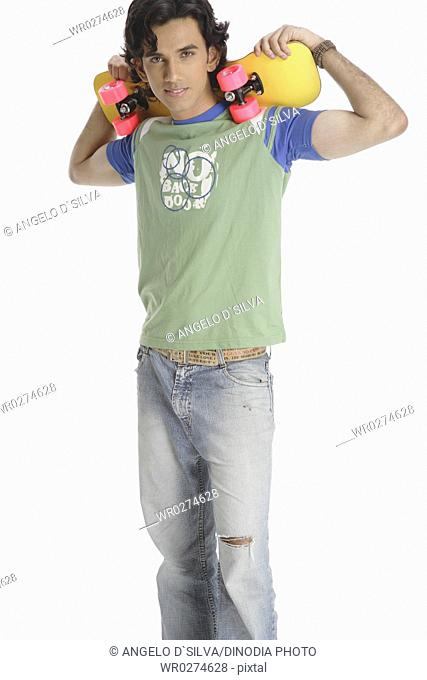 Teenage boy standing with skate board holding on shoulder MR 687T