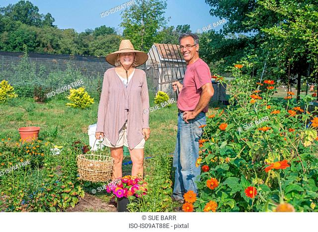 Portrait of male and female farmers in garden