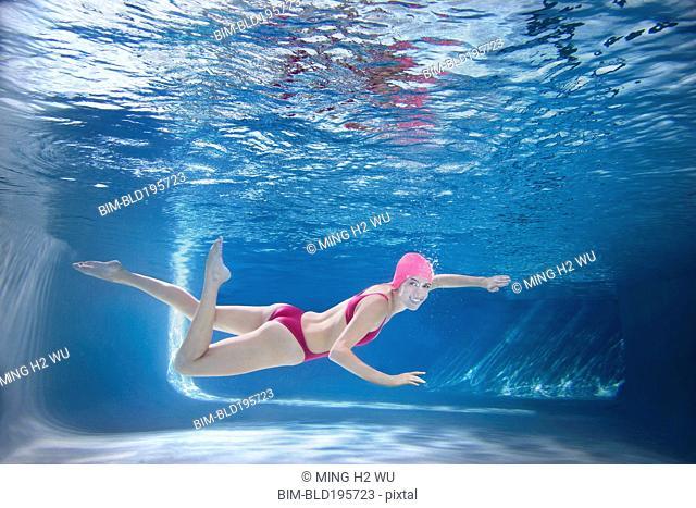 Caucasian woman in bikini swimming underwater