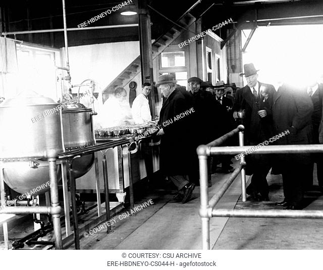 Men wait in line for food at a municipal lodging house. Police Commissioner Edward P. Mulrooney stands with coffee second from