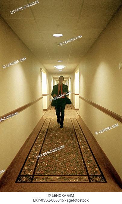 Man running down hotel hallway