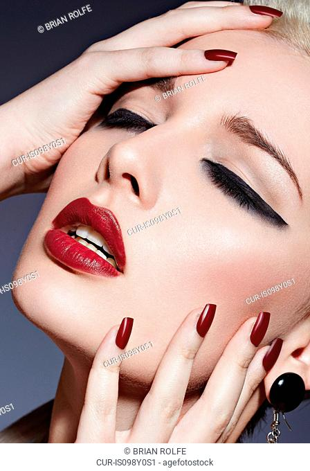 Young woman with red lipstick and nail varnish touching face, portrait