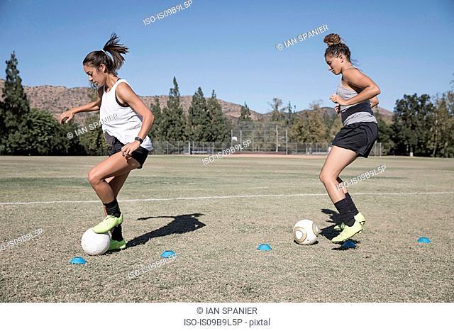 Women dribbling footballs