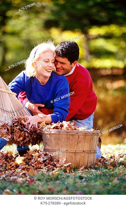 playful couple and a basket of leaves
