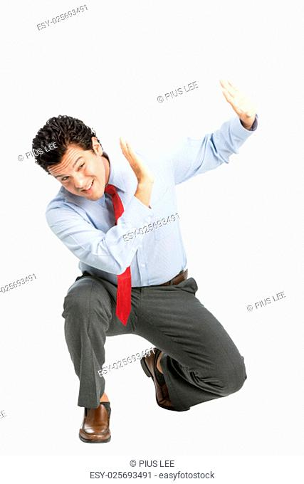 An intimidated latino man office worker in business attire crouching putting hands to shield in self defense, protecting against verbal
