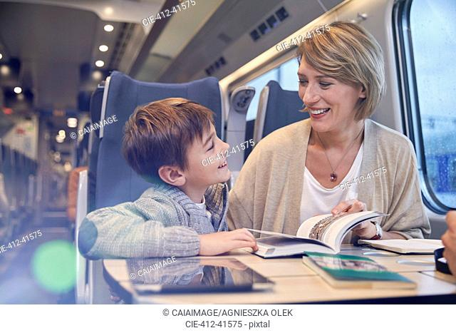 Mother and son reading travel guidebook on passenger train