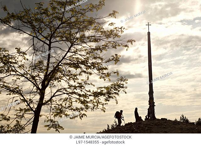 Silhouette of pilgrims leaving stones at the base of Cruz de Ferro near the village of Foncebadon along the Camino de Santiago