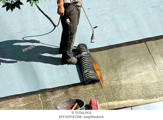 roofer with a gas burner on a roof