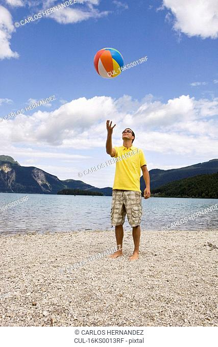 A young man throwing up a beach ball