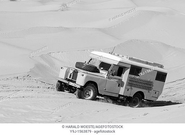 Africa, Tunisia, nr  Tembaine  Desert traveller driving an ex-army 1966 Land Rover Series 2a Ambulance camper conversion through a sandfield with dunes close to...