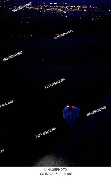 Female trail runner using head torch running up dirt track at night, Colorado Front Range, Boulder, USA